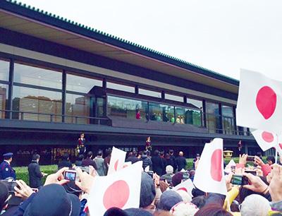 ベランダに立つ皇室一族と旗を振る一般参賀者たち